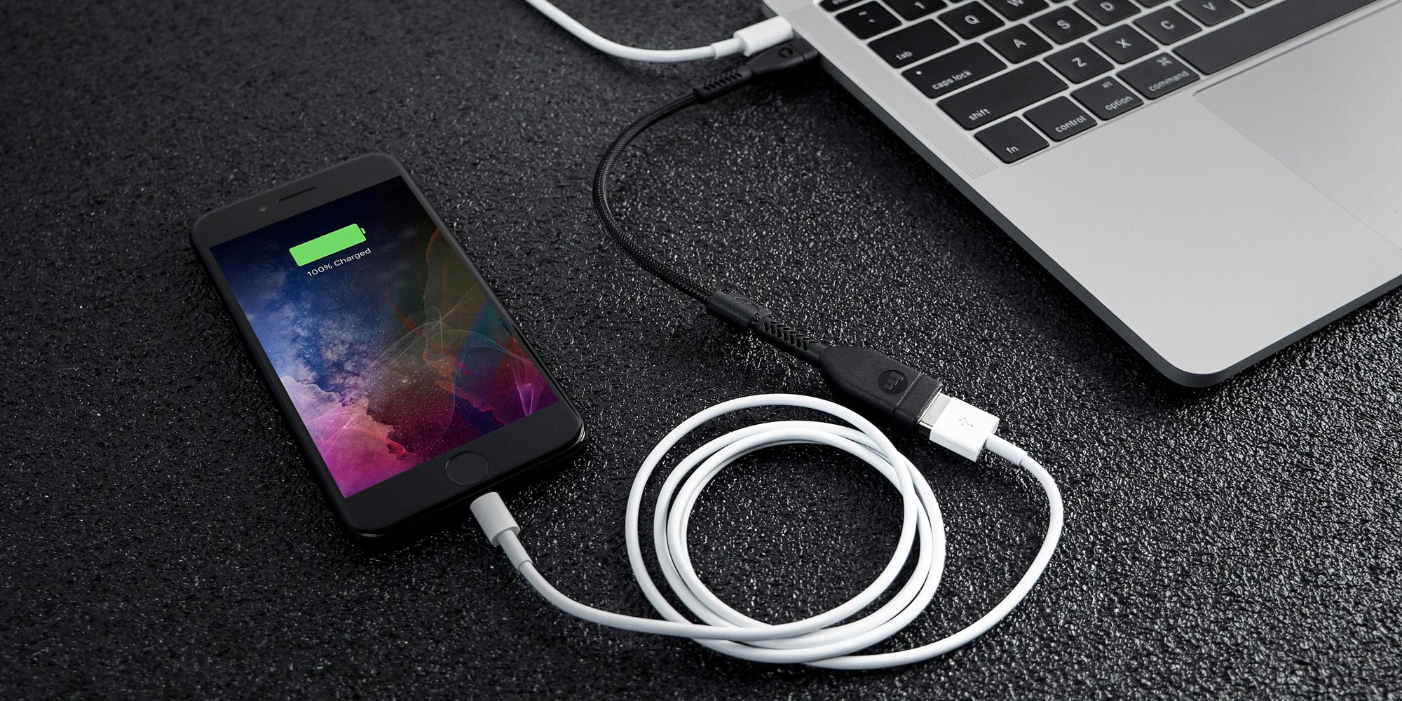 A phone plugged into a PRO adapter switching USB-C to USB-A 1 to charge from a computer