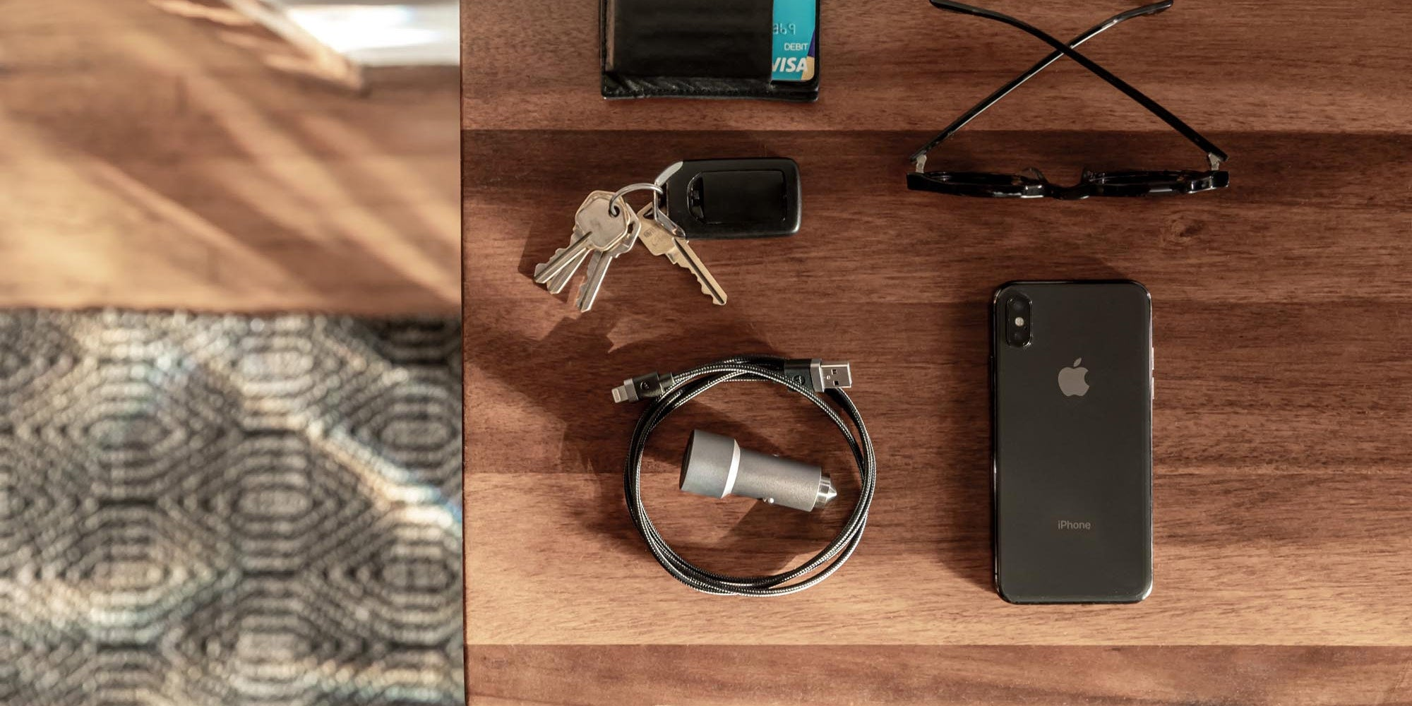 A mophie dual usb car charger on a table next to an iPhone and a set of keys