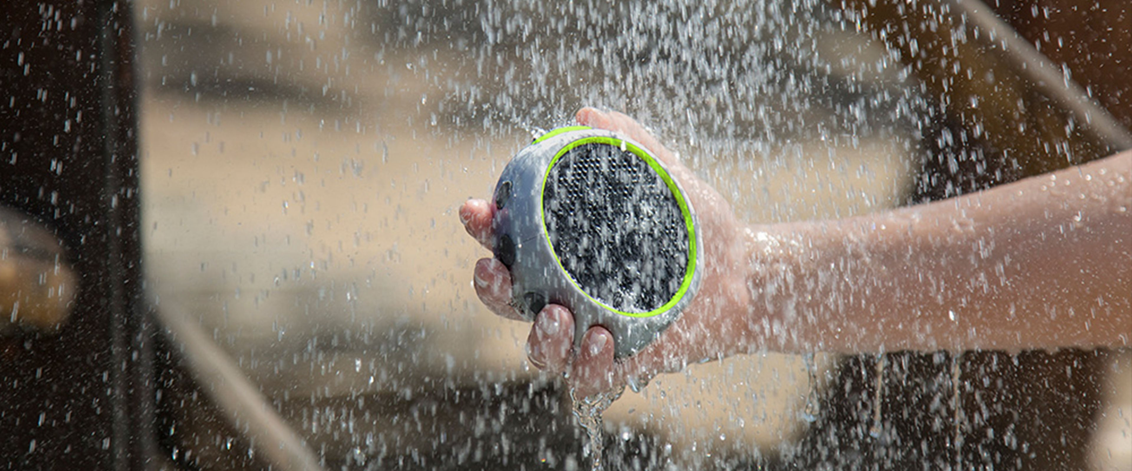 Person holding a Braven speaker in a rainfall of water