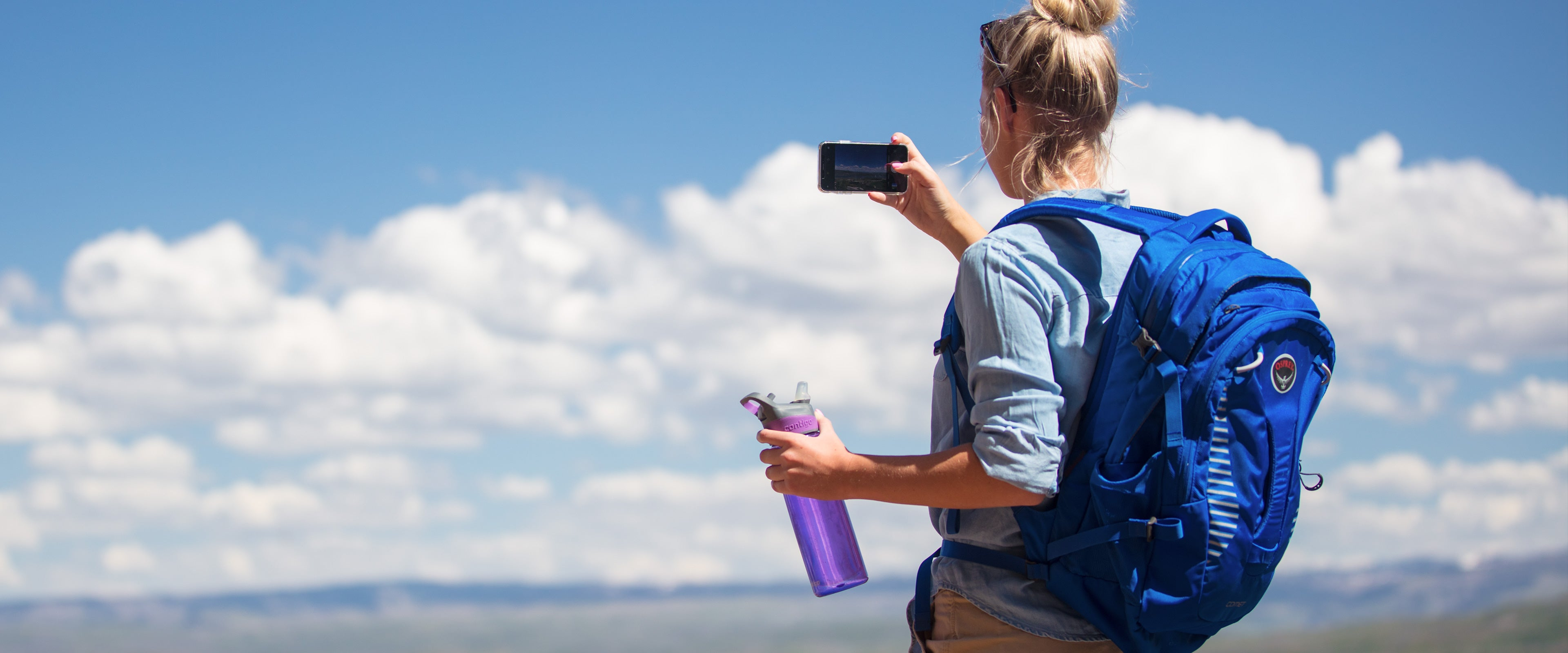 Woman using her phone to take a landscape picture