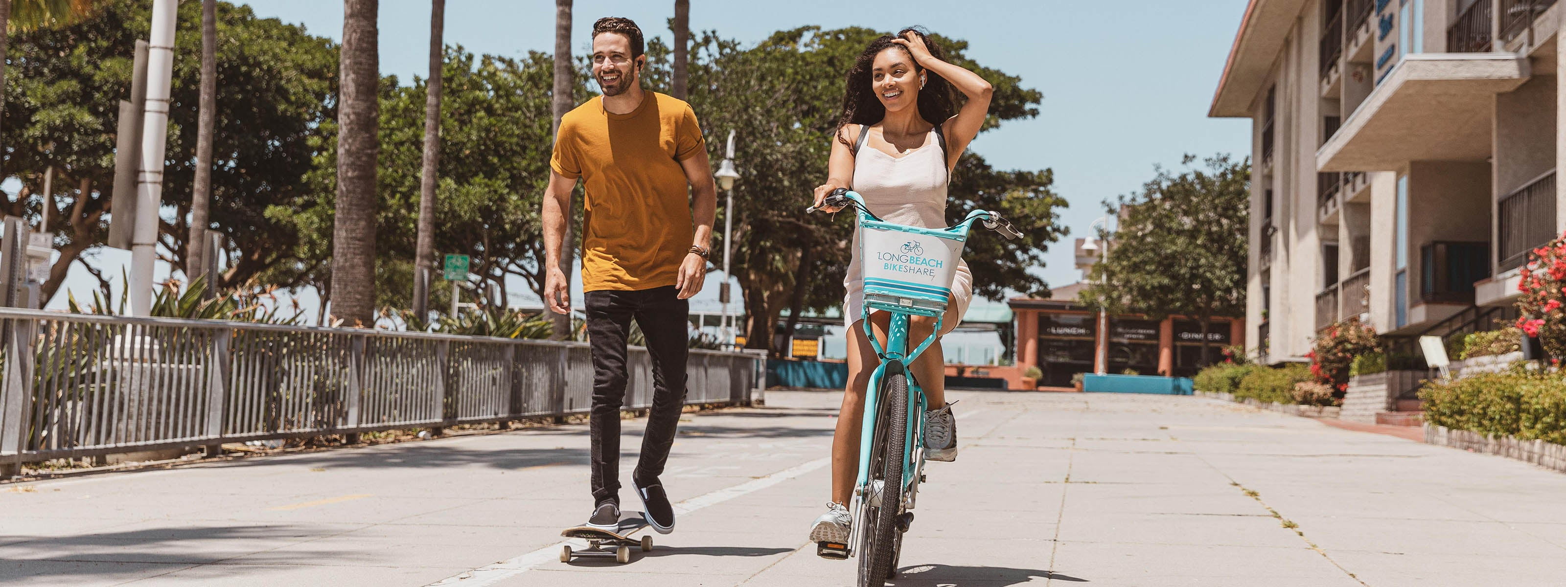 girl biking and guy skateboarding
