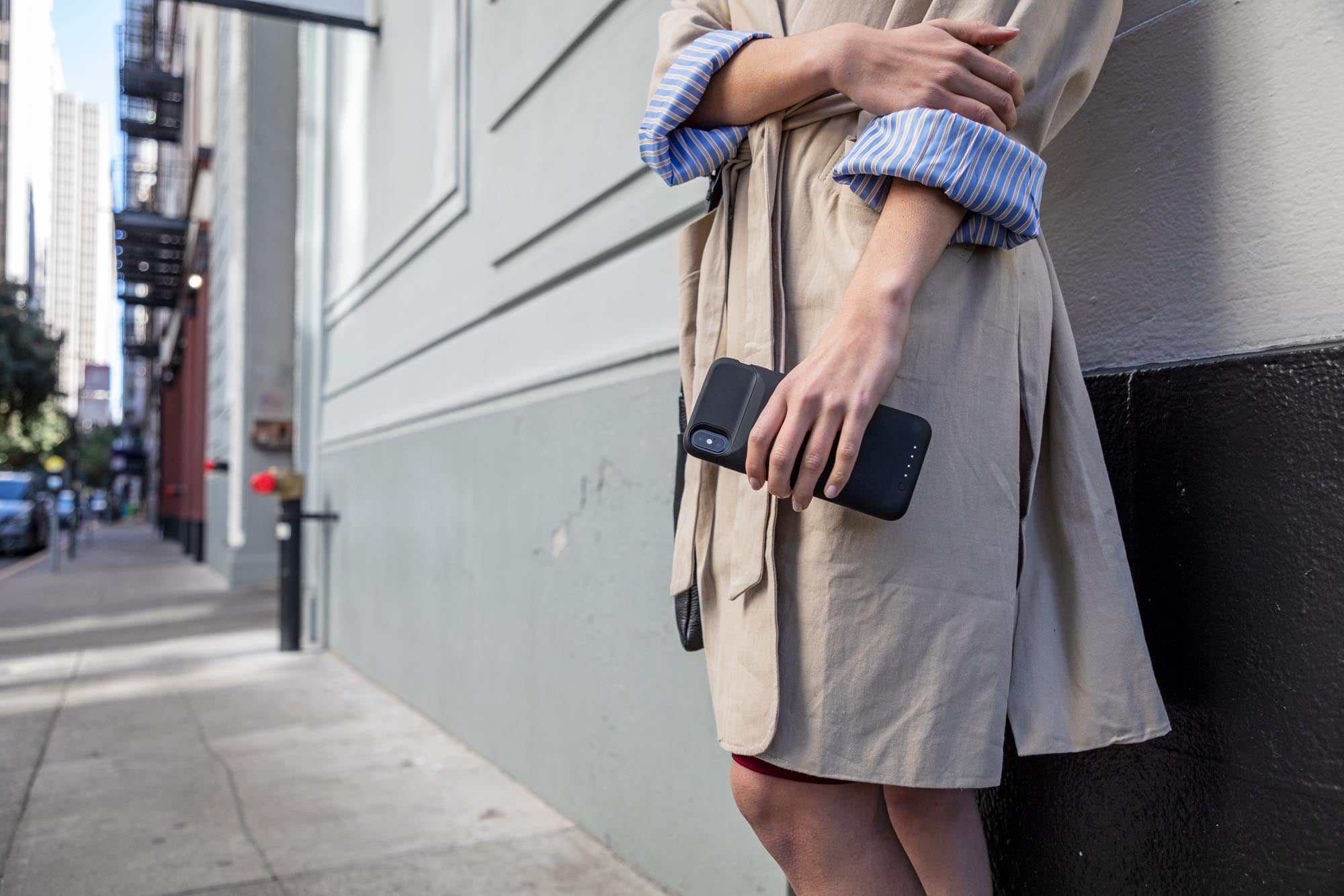 Woman holding her phone while next to a building on a sidewalk