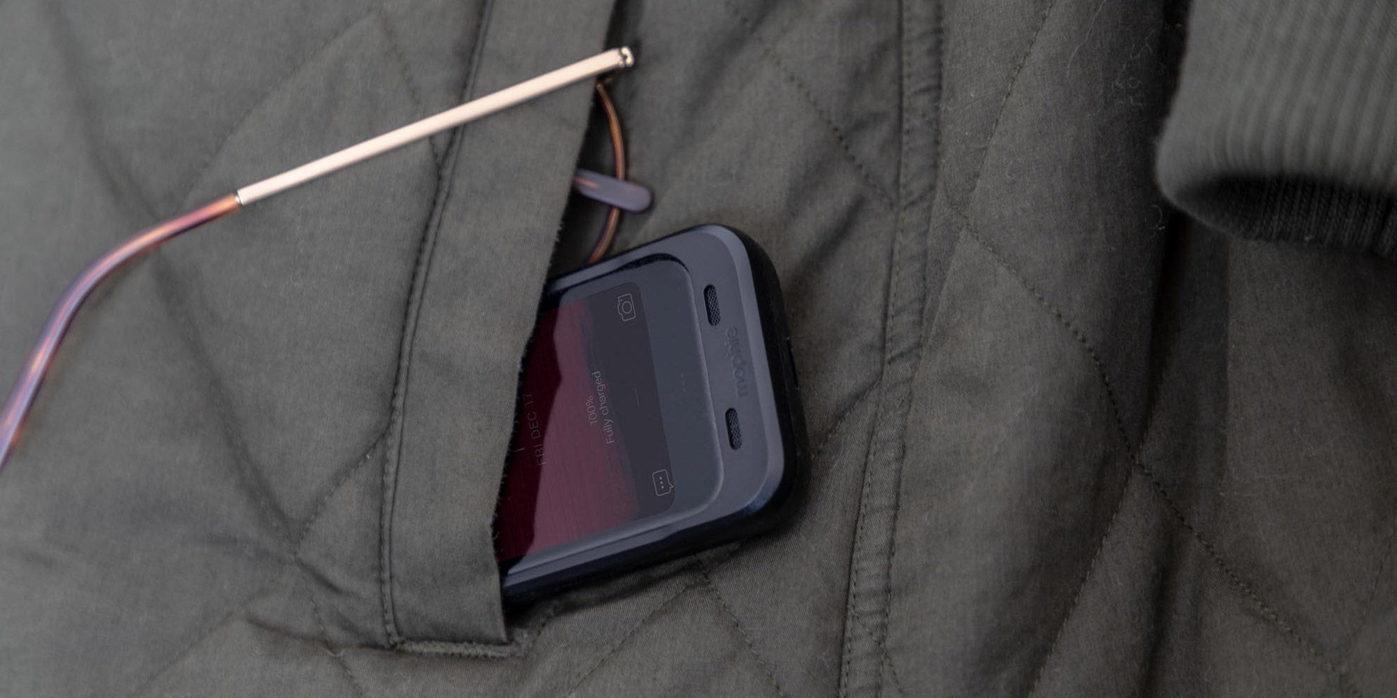 A Palm phone with a mophie juice pack peeking out of a coat pocket
