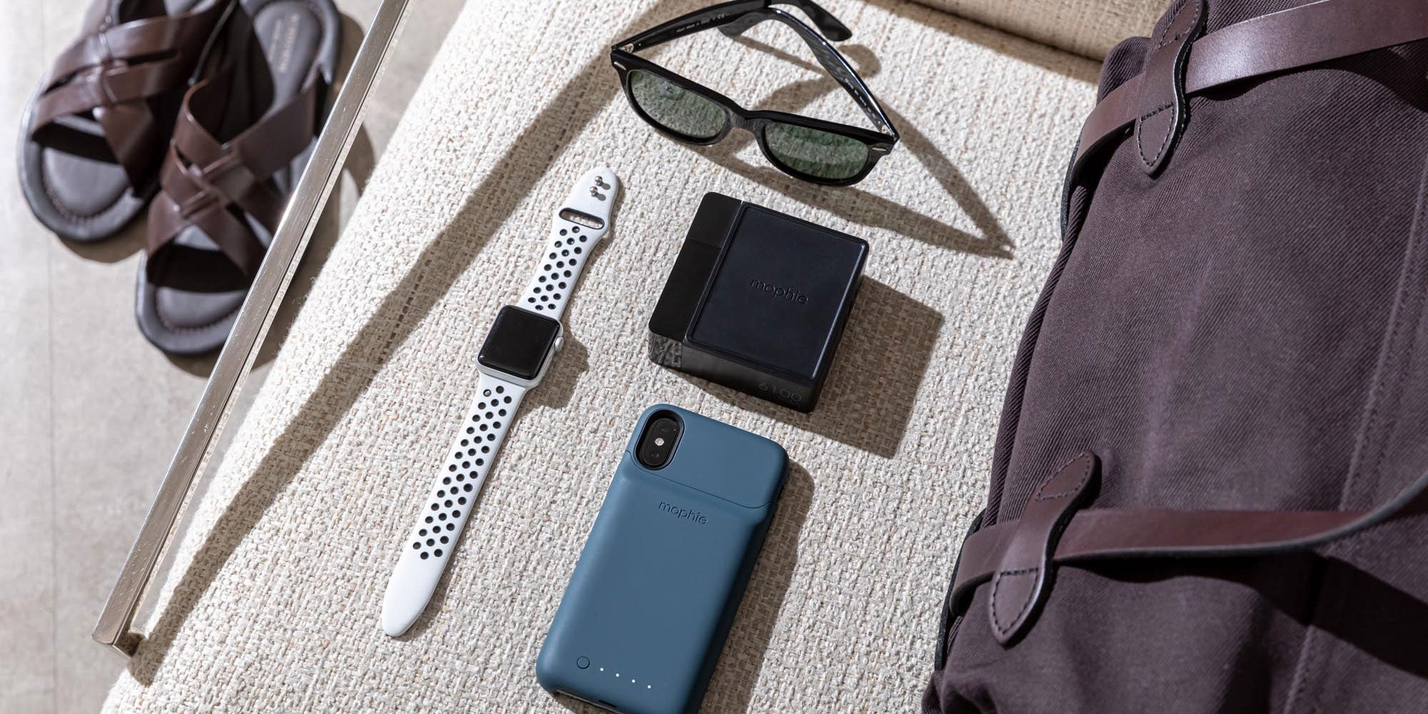 mophie powerstation hub on a chair next to an apple watch, a phone, sunglasses, a duffle bag, and sandals