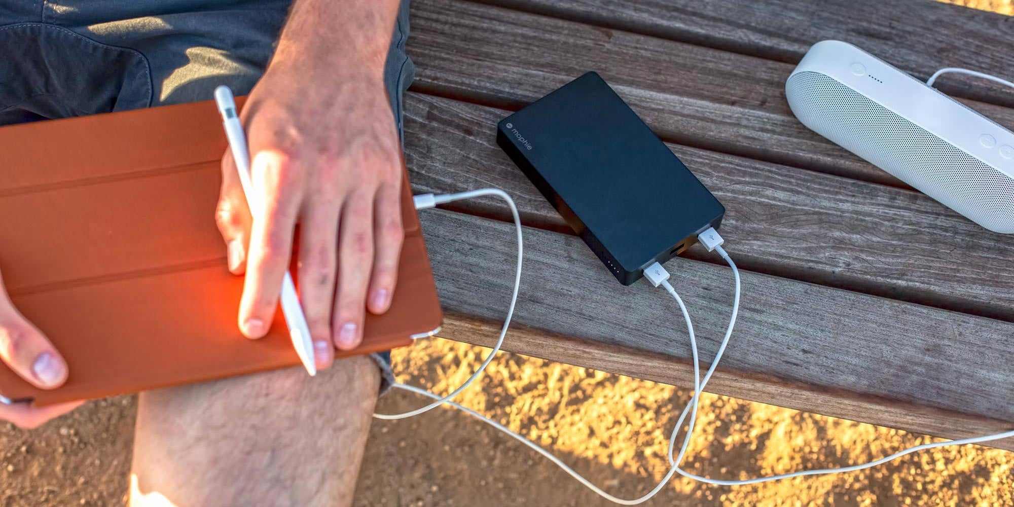 mophie powerstation XXL on a park bench charging multiple devices