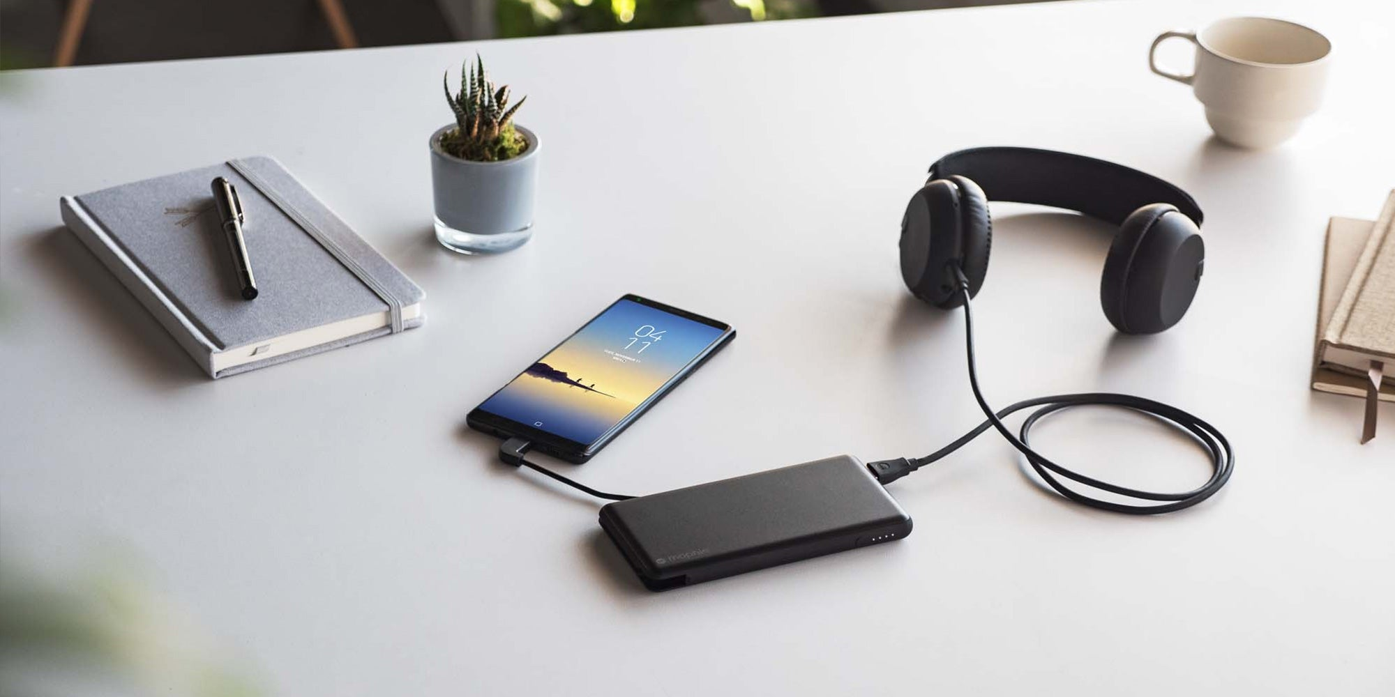 A phone and headphones lying on a table charging with a powerstation plus XL