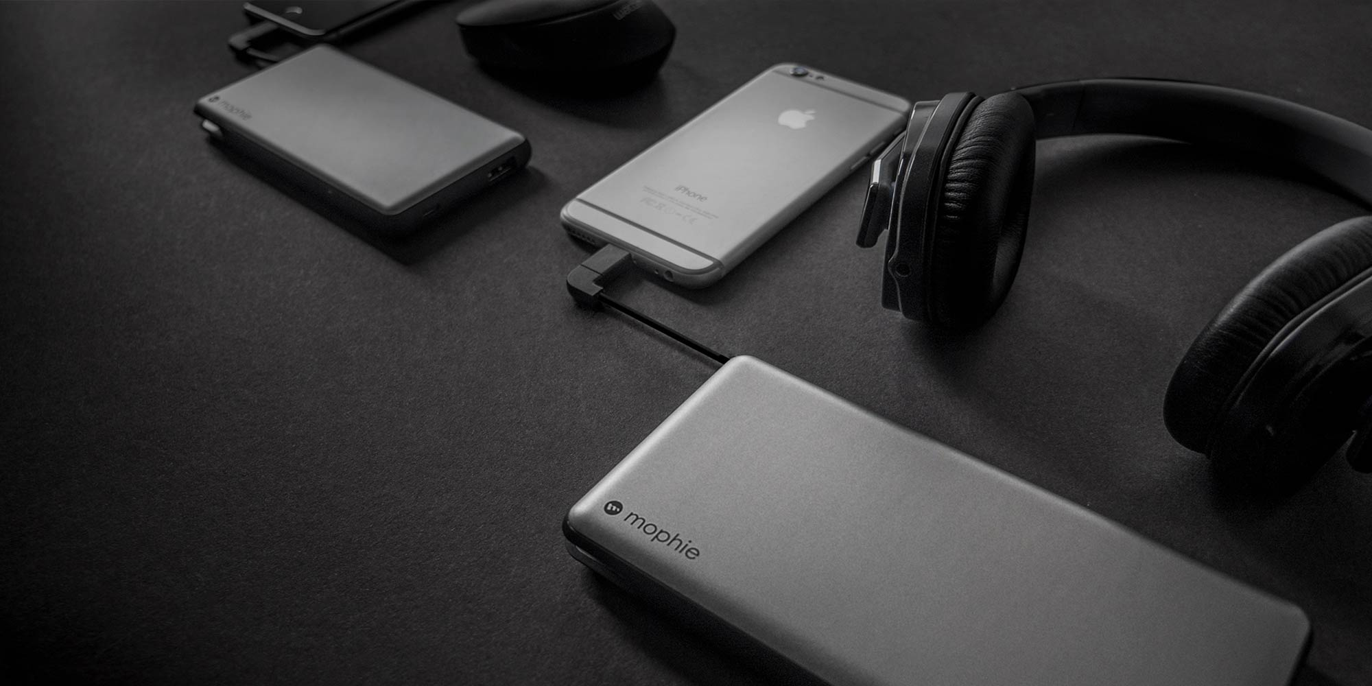 Two iPhones, a mouse, headphones, and two mophie powerstation plus xls on a black table