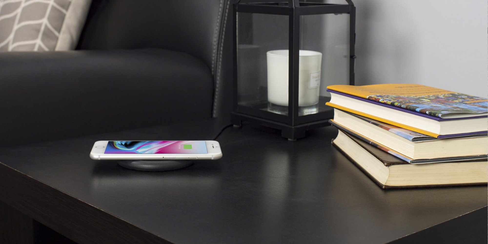 An iPhone charging wirelessly on a mophie charging pad