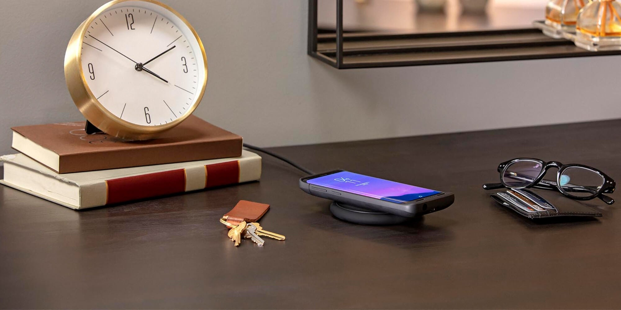 A phone charging on a table next to a clock, books, a wallet, keys, and reading glasses