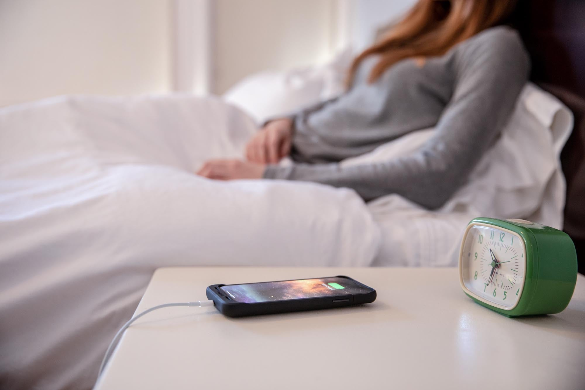 Woman in a bed next to a phone charging on the nightstand
