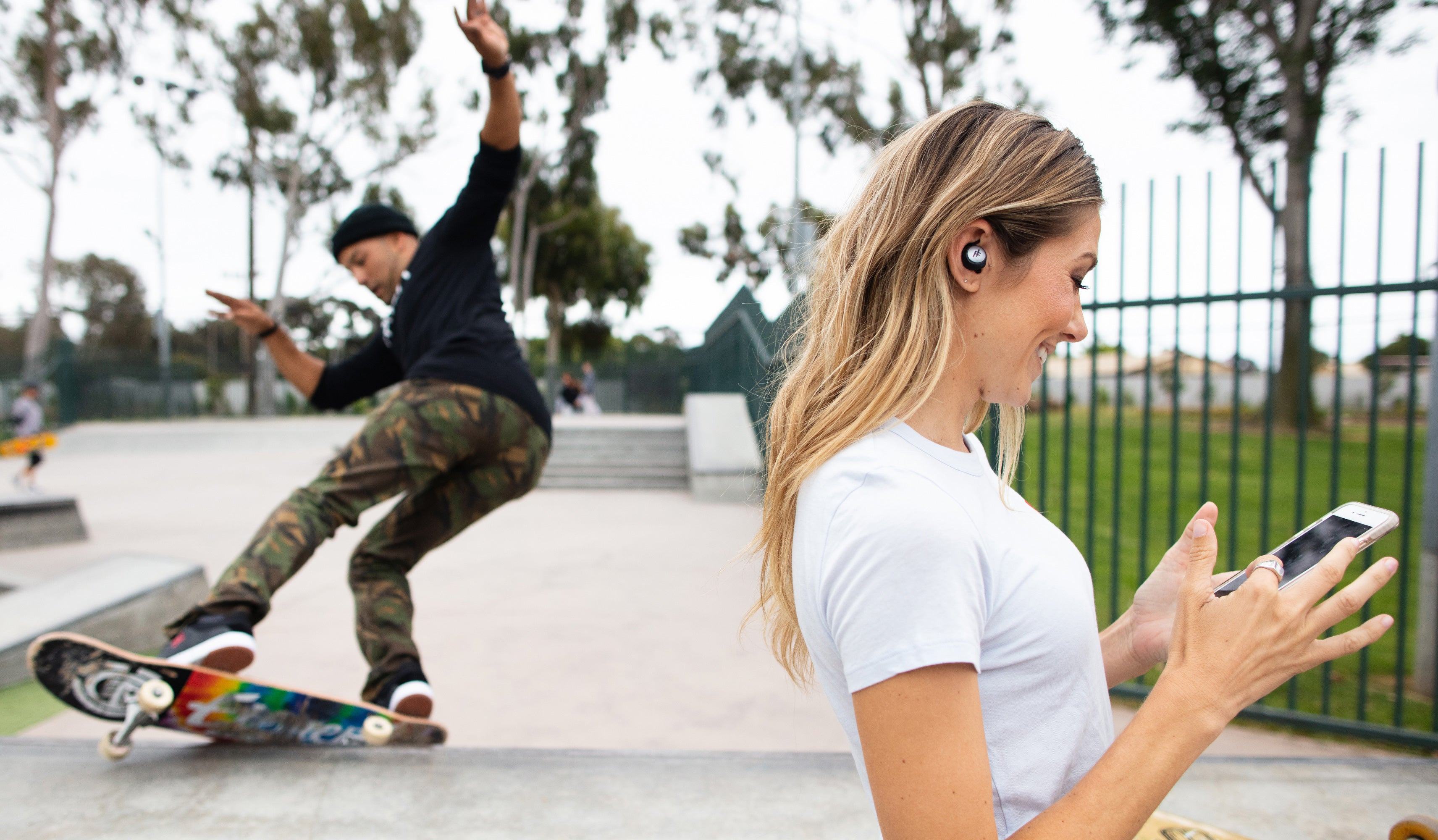 Woman using iFrogz Airtime earbuds in a skatepark. Man doing a skateboard trick behind her.