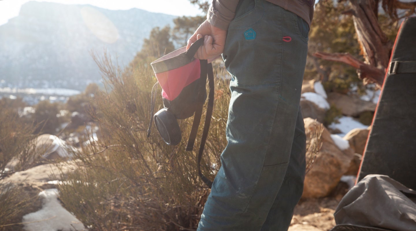 Woman holding a rock climbing chalk bag with a speaker attached to it