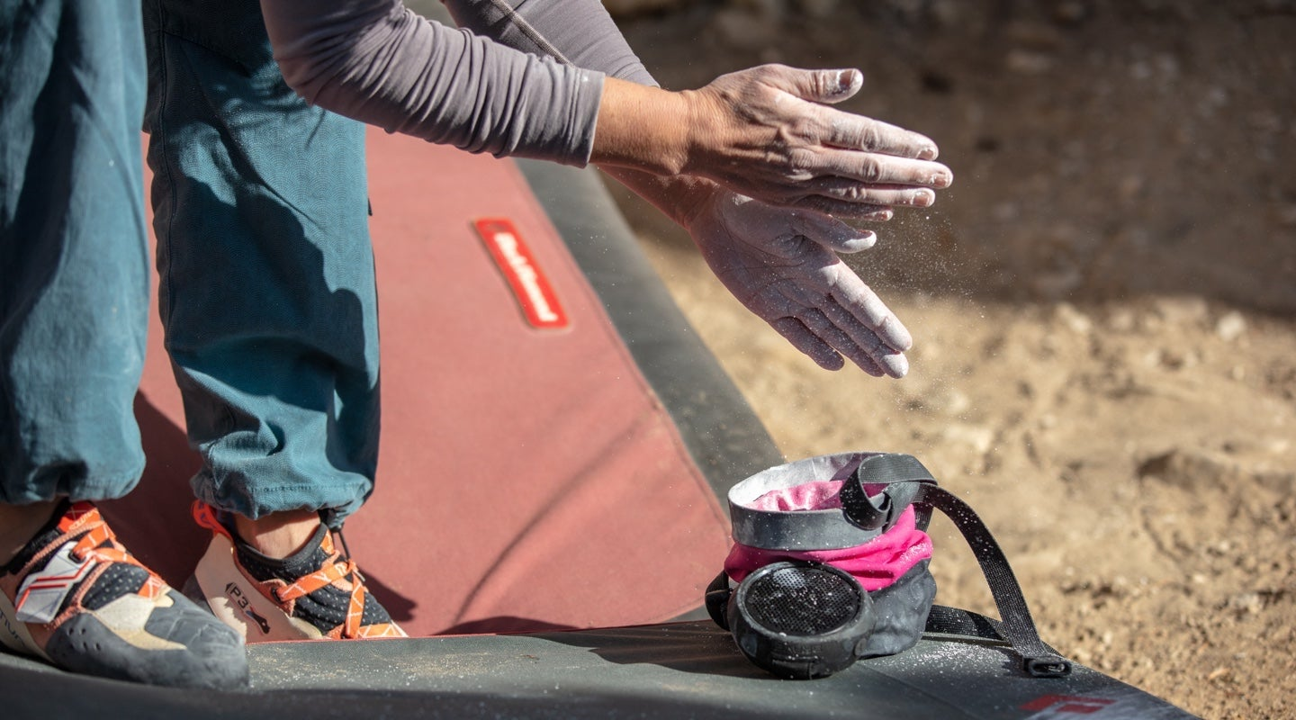 Woman chalking her hands from a rock climbing chalk bag with a braven speaker attached