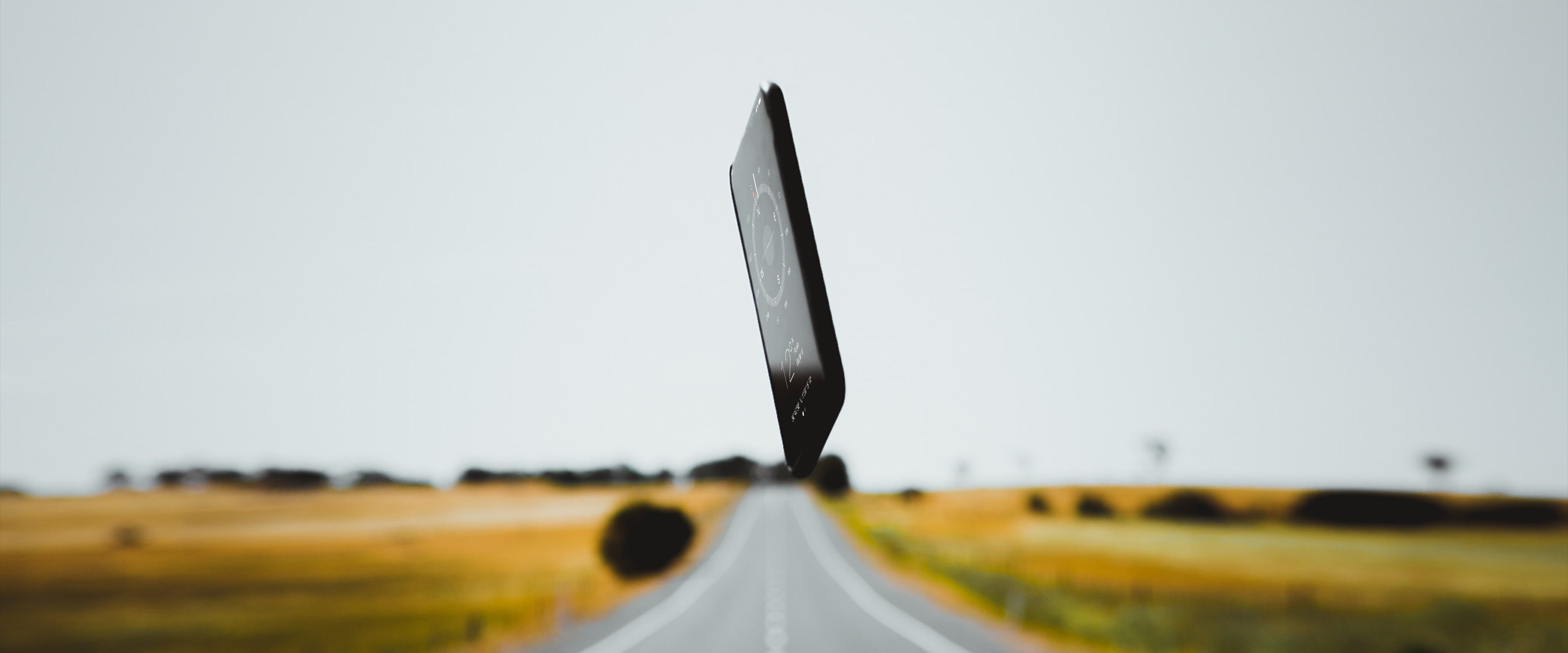 A phone falling to the ground on a country road