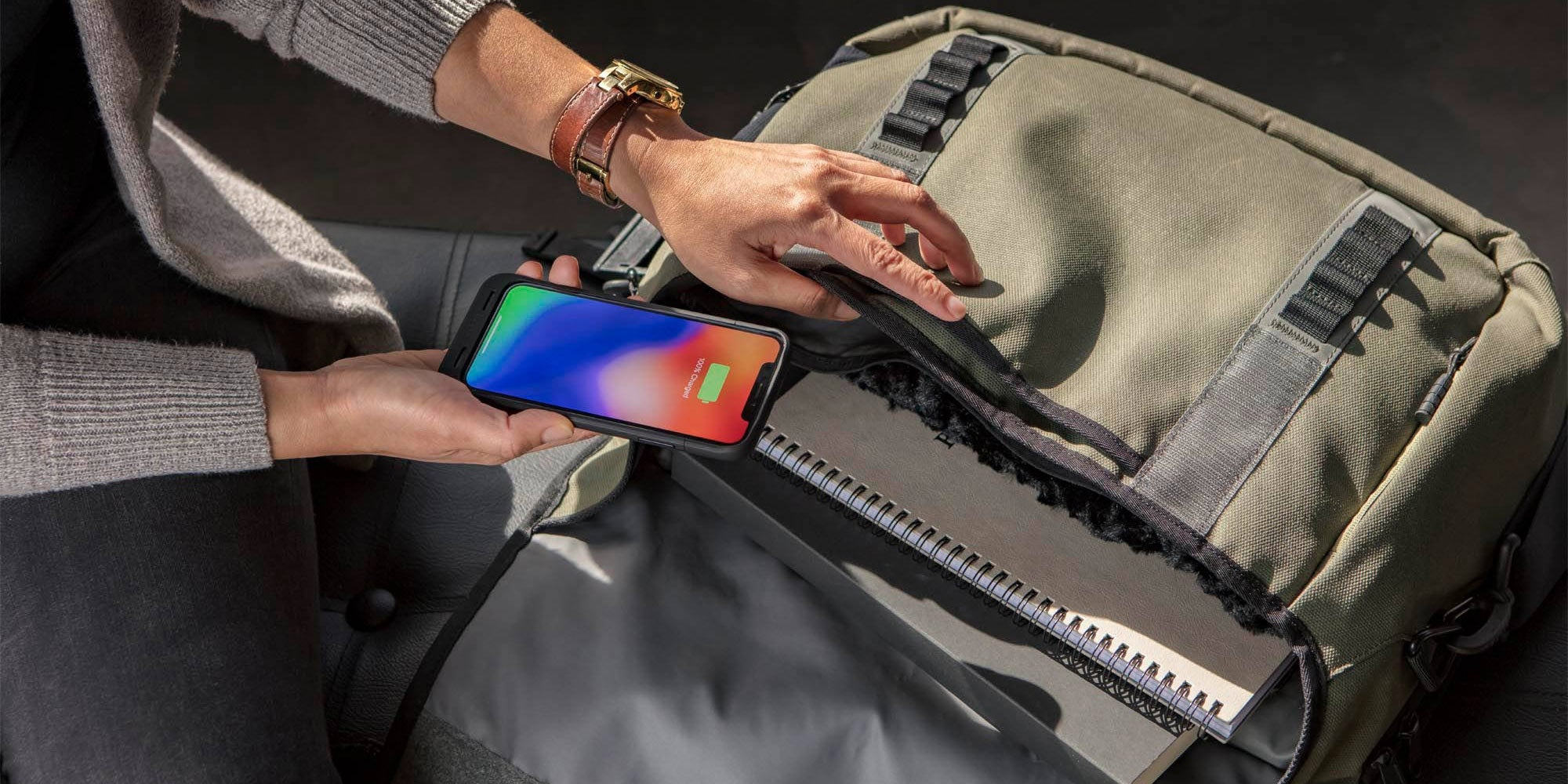 A woman putting an iPhone with a mophie juice pack air charging case on it into a laptop bag