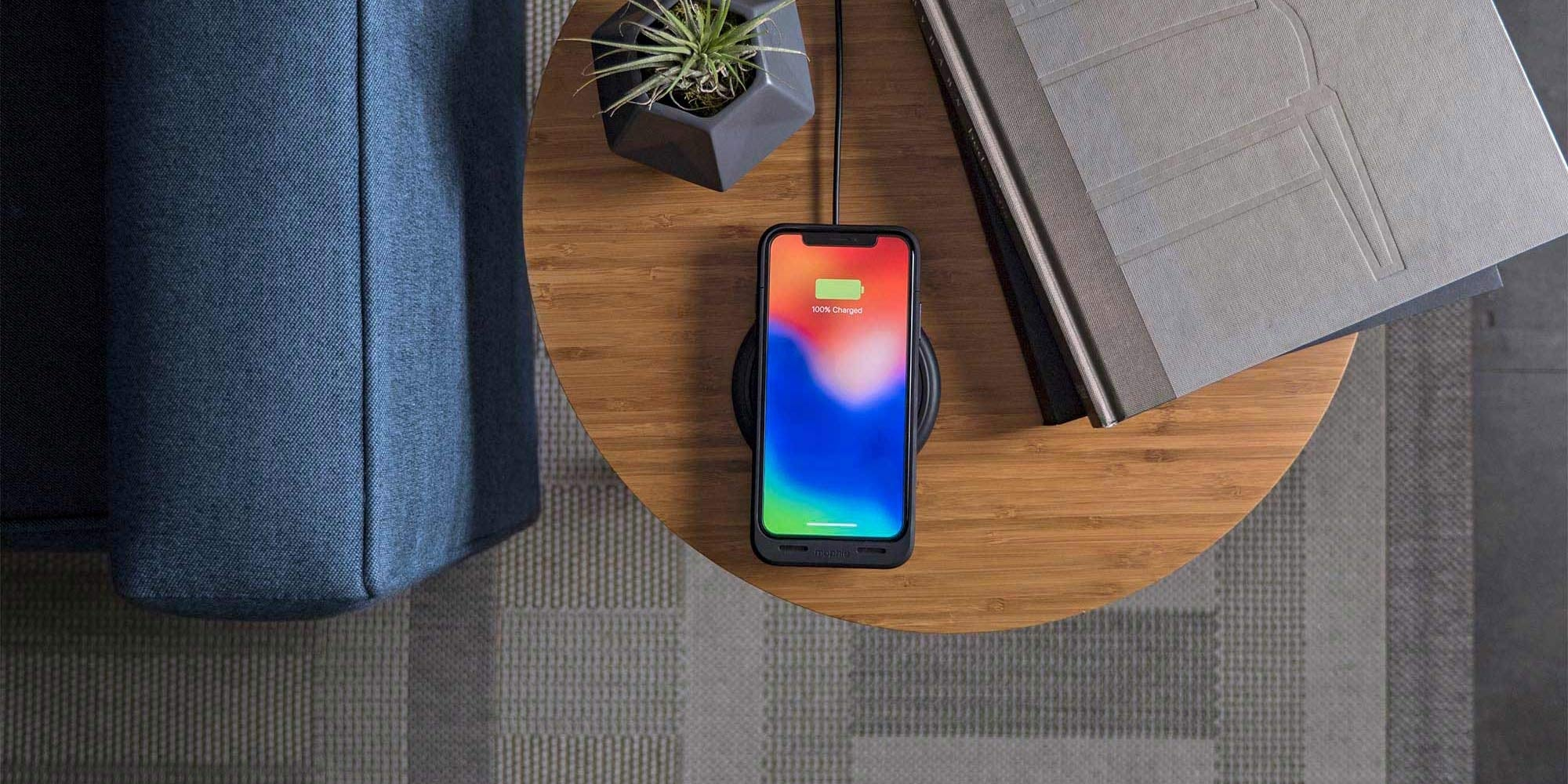 An iPhone with a mophie juice pack air charging case charging on a mophie charge pad