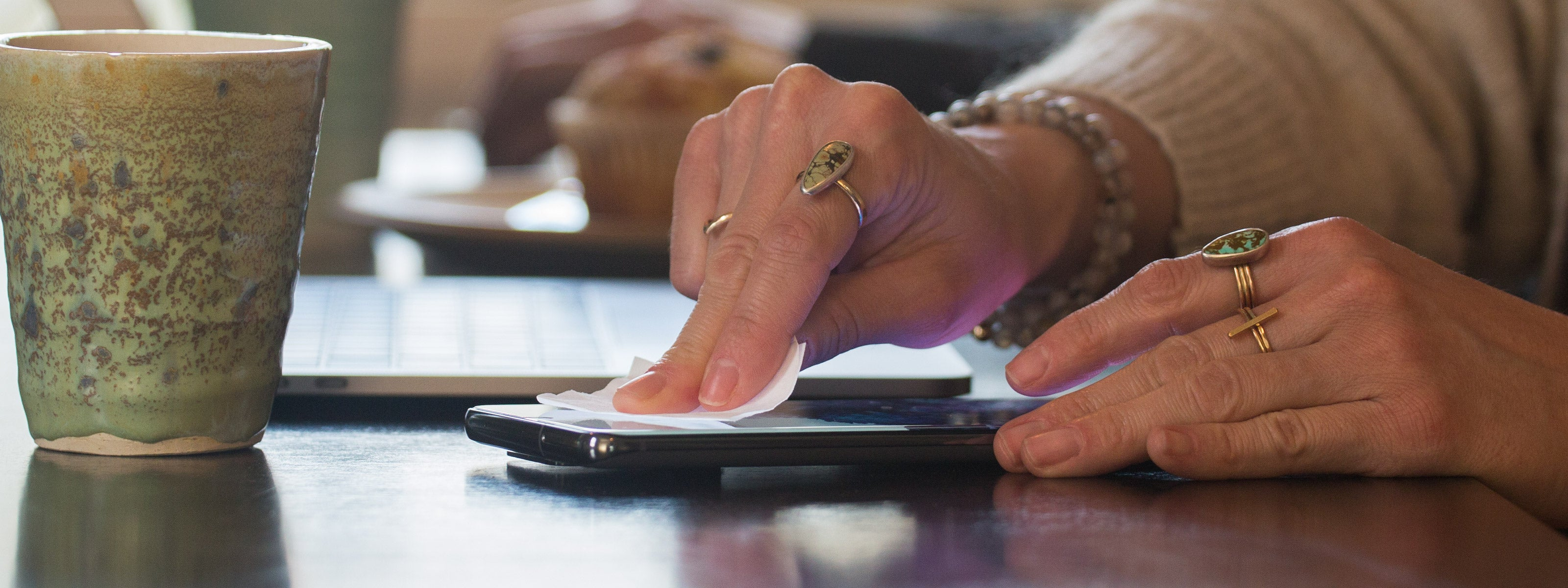 woman in a cafe wiping down her phone