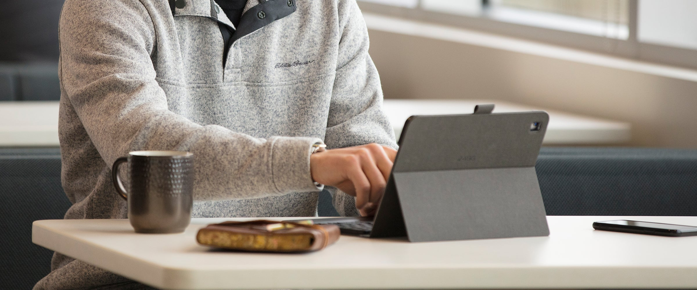 Man using an iPad with a Messenger Folio case on it