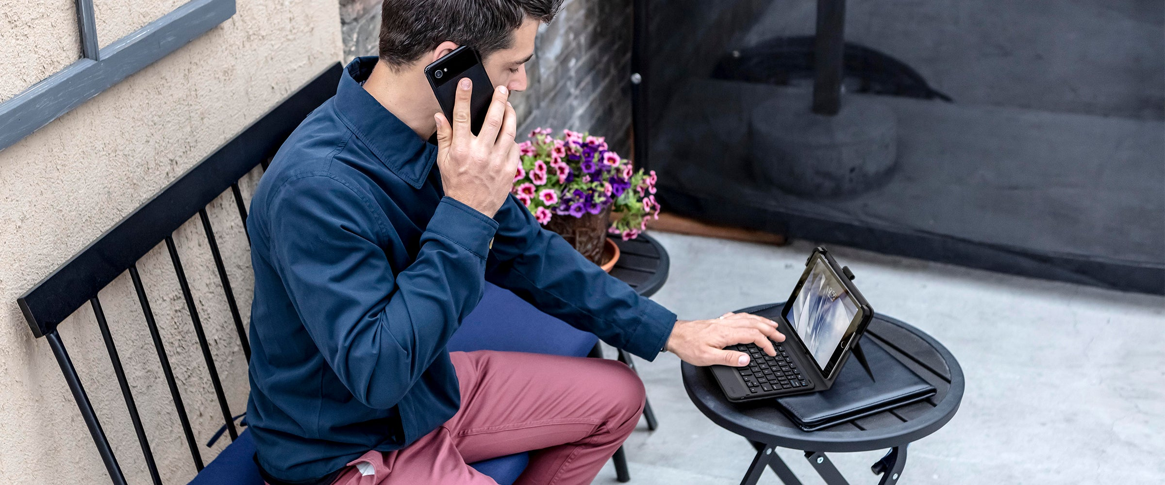 Man talking on a phone while using an ipad with a messenger folio keyboard