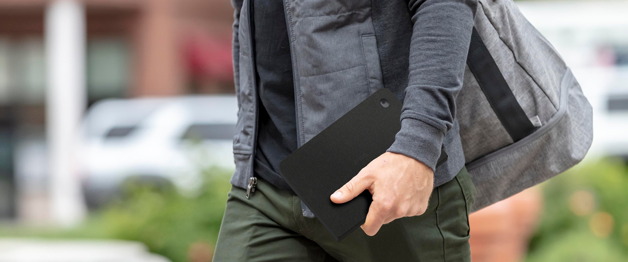 Man walking with an ipad in a messenger folio case