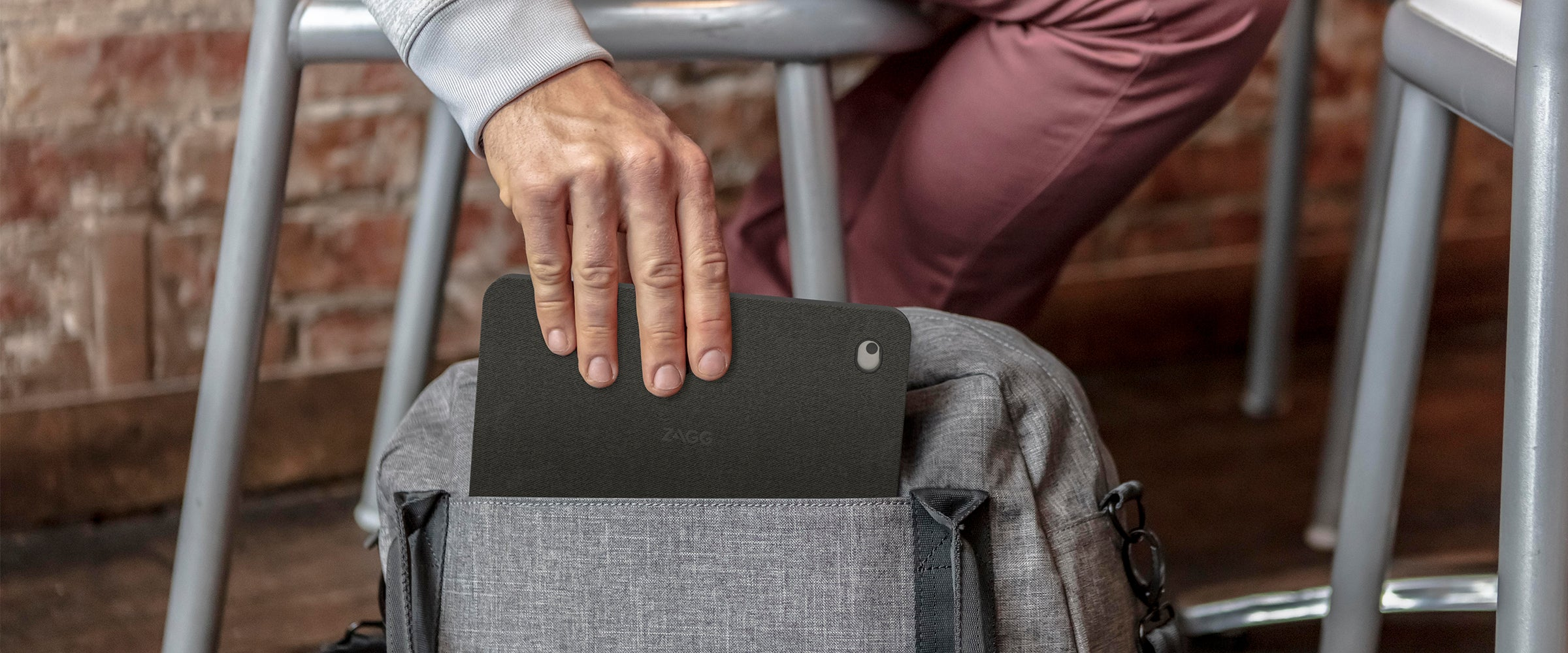 Man putting an iPad with a messenger folio case into a bag