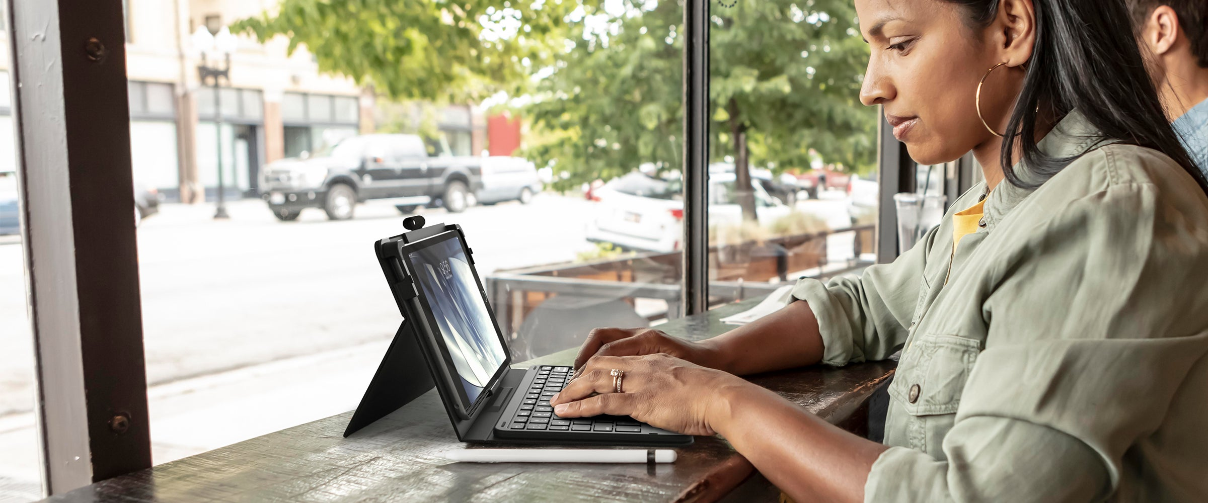Woman by windows working on an iPad with a messenger folio case