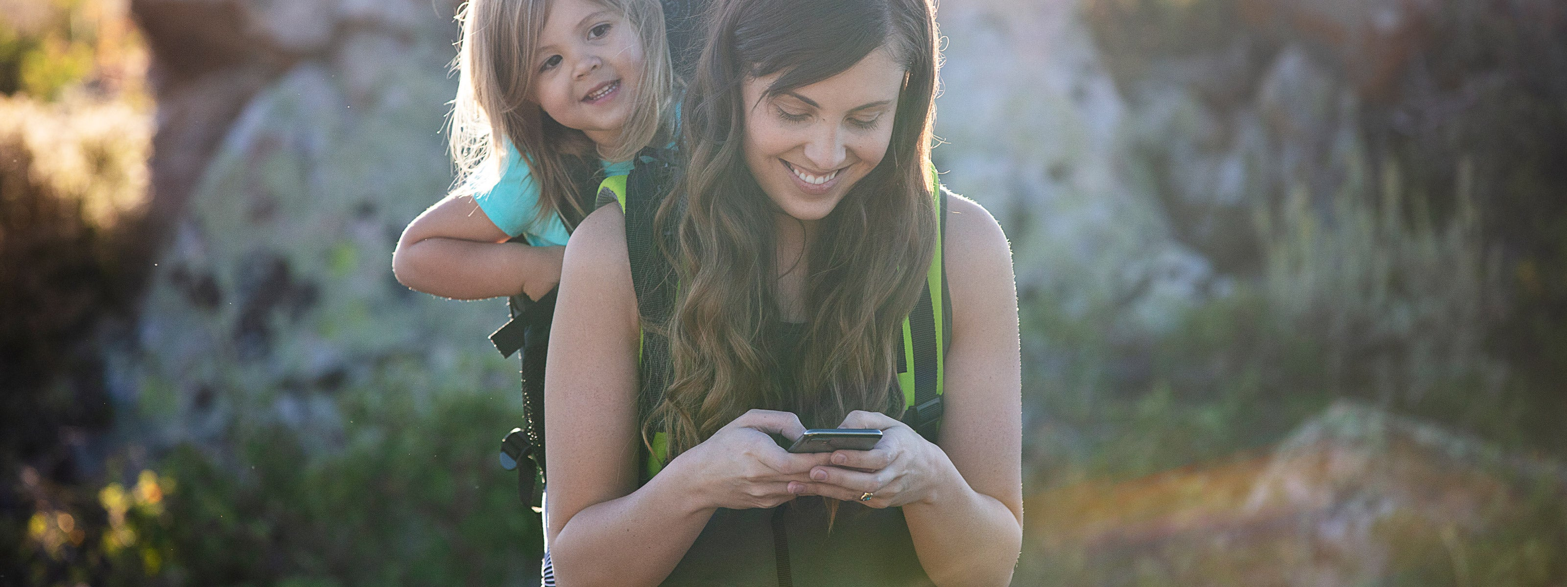 mother carrying daughter with iphone