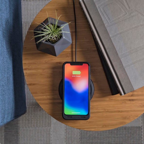 iPhone X charging on a wireless charging base