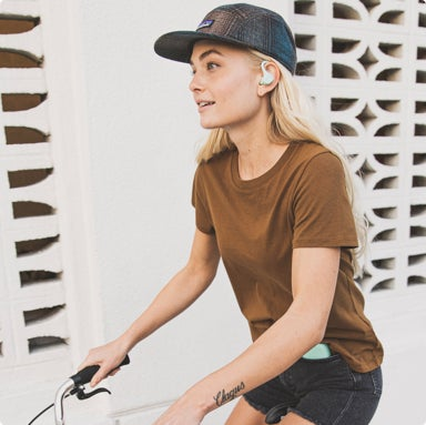 Woman outside with headphones in her ears ridng a bicycle