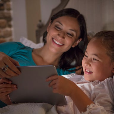 Woman and a girl looking at a tablet screen
