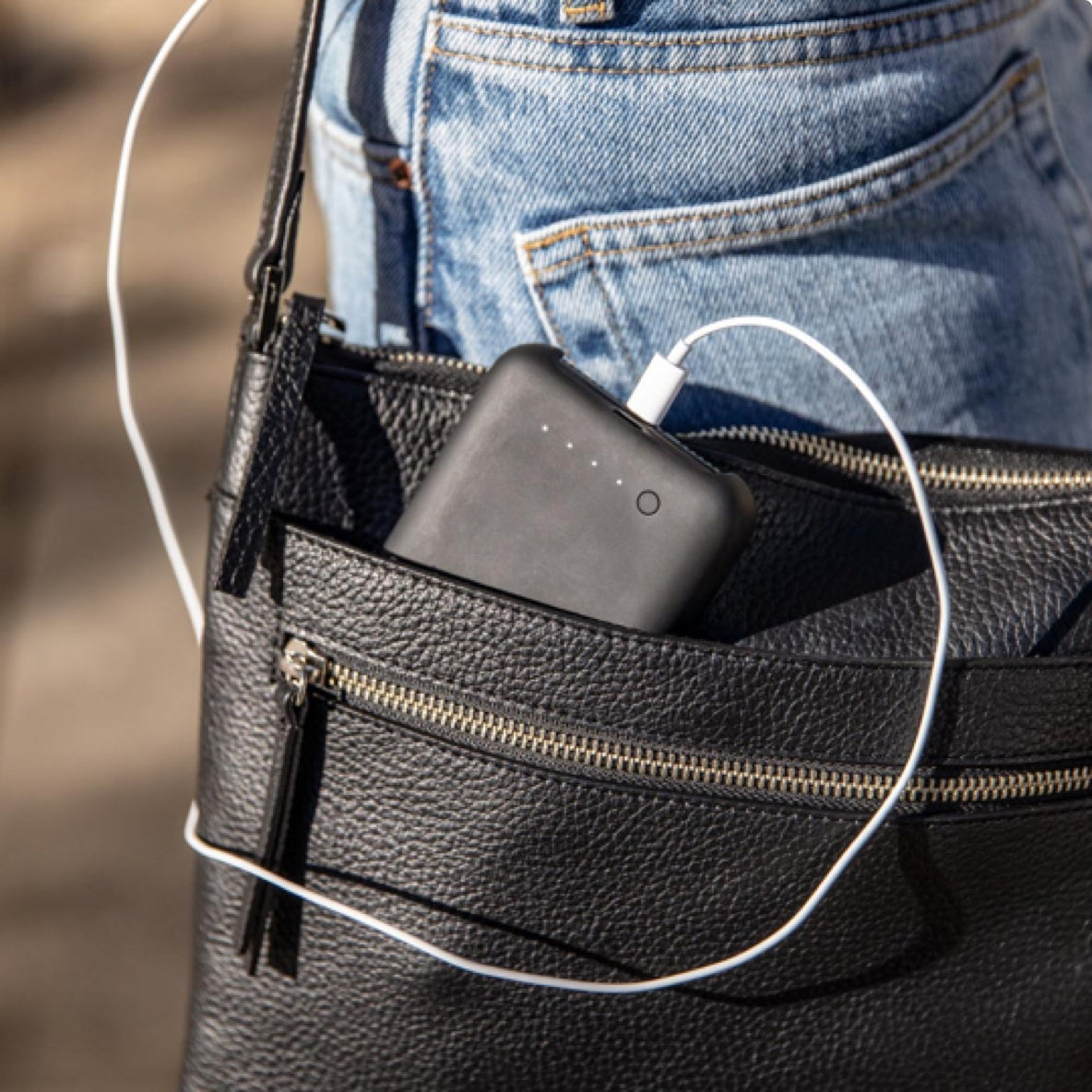 A mobile phone peaking out of a purse