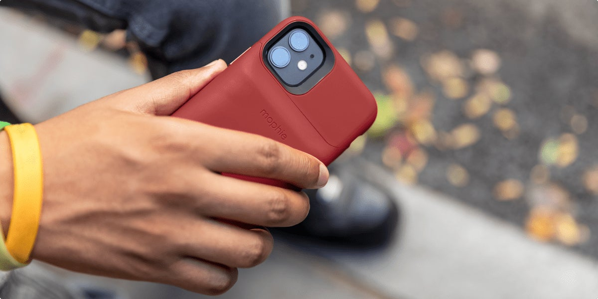 Person taking a photo with their mobile phone with a juice pack access on it