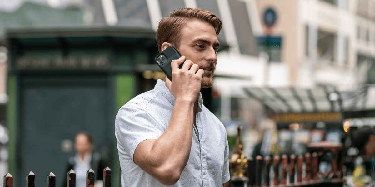 A man holding a mobile phone while listening to headphones